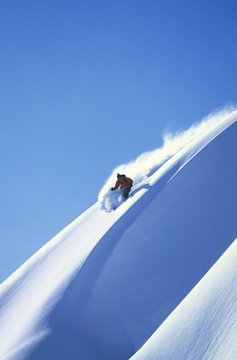 Man skiing on steep slope against clear blue sky