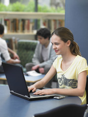 Happy teenage girl using laptop in library