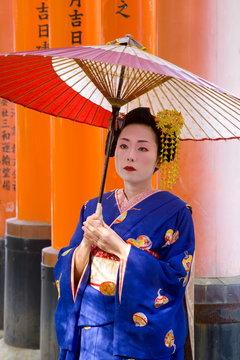Portrait of a geisha holding an ornate red umbrella in front of a line of red torii gates, Fushimi-Inari Taisha, Kyoto, Kansai Region, Honshu, Japan