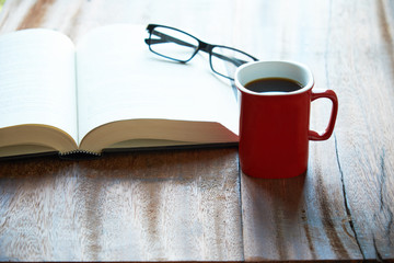 A cup of coffee with book and glasses on wooden table. Enjoy reading.