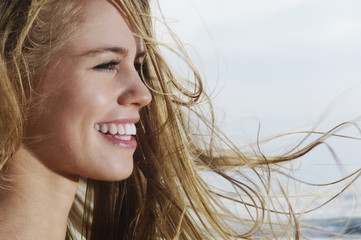 Closeup profile of a smiling young woman looking away with blond hair blowing in wind