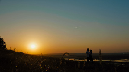 loving couple - brave young man and beautiful girl at sunset silhouette, wide angle