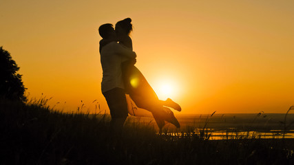 Romantic Silhouette of Man Getting Down on his Knee and Proposing to Woman  high hill - Couple Gets Engaged at Sunset -  Putting Ring  Girl's Finger,