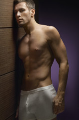 Portrait of a shirtless man wearing underwear leaning by wooden wall