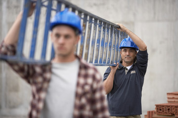 Closeup of two construction workers carrying ladder
