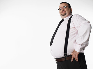 Portrait of a smiling overweight businessman standing with hand on hip against white background