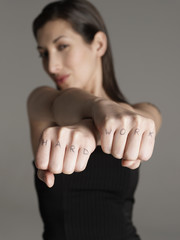 Blurred young woman showing fists with 'hard work' text against gray background