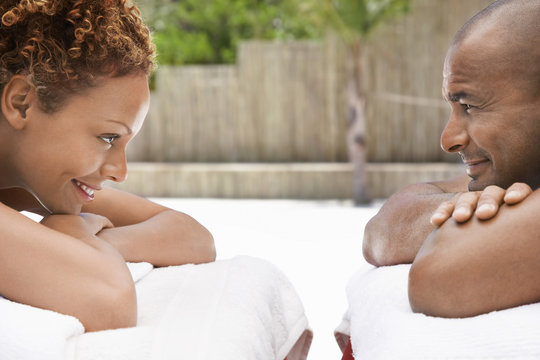 Happy African American couple lying face to face on massage tables at spa