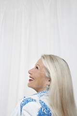 Side view of a happy senior woman looking up against white background