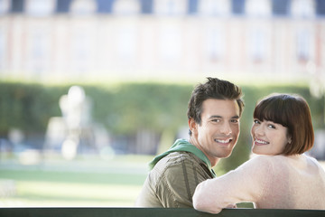 Portrait of a smiling young couple sitting on park bench