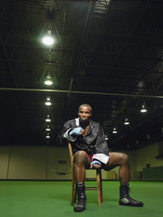 Full length portrait of an African American boxer sitting on chair