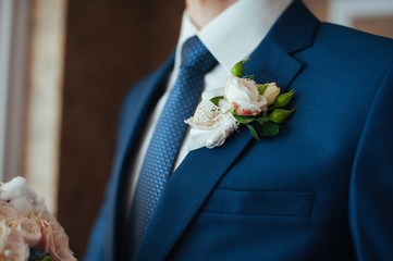 the groom in a blue suit with  tie
