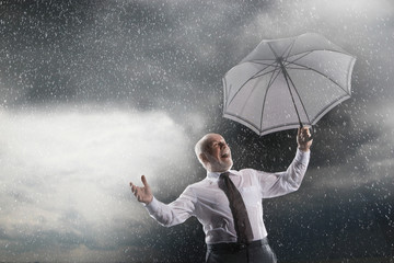 Low angle view of a middle aged businessman with umbrella laughing in storm