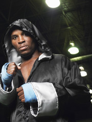 Portrait of an African American boxer in robe with hood up clenching fists