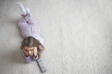 Top view of a little girl lying on rug with remote control