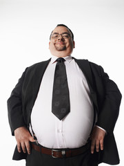 Portrait of a smiling overweight businessman standing with hands on hips against white background