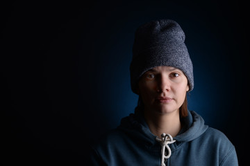 Young girl in a knitted cap on a dark background.