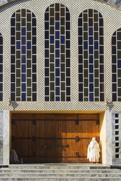 Pilgrim at doors of St. Mary of Zion new church, built by Haile Selassie in the 1960s, Axum, Ethiopia