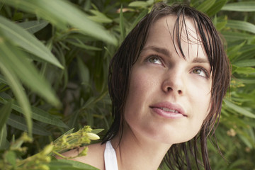 Closeup of beautiful woman looking out from shrub