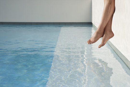 Low section of woman sitting on edge of swimming pool