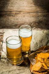 Beer in mug, glass on wooden background