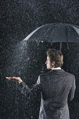 Rear view of a businessman sticking hand out from under umbrella to feel the rain
