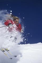 Female skier skiing through powdery snow on ski slope against clear blue sky