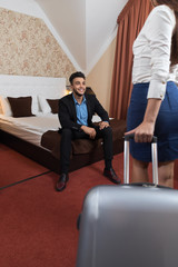 Latin Businessman Sitting At Bed In Room Businesswoman With Luggage Suitcase Business Man And Woman Arriving To Hotel