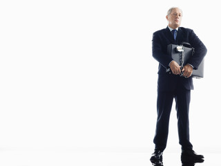 Full length of businessman carrying chained briefcase over white background