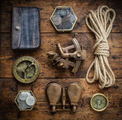 Fototapete - Vintage compass, sextant, binoculars, rope and coins on the old wood table. Adventure stories background. Retro style.