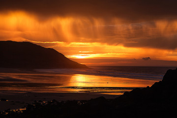 Sunrise at Caswell Bay Dramatic clouds at Caswell Bay, one of the most popular and easily accessible beaches on the Gower peninsula in Swansea