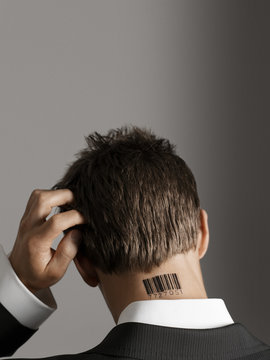 Rear view of a businessman with barcode tattoo on neck scratching his head against gray background
