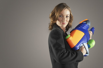 Portrait of a smiling businesswoman standing with water gun against gray background
