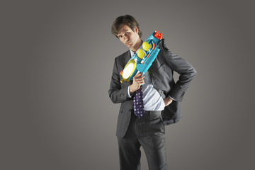 Portrait of a serious businessman standing with water gun against gray background