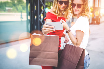Summer sunny day.Two young women standing outdoors with shopping bags and make selfie on smartphone,looking on screen of phone.Girls showing photos on smartphone.In background,modern glass building.