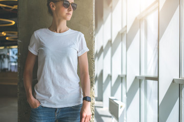 Front view. Young woman in sunglasses, white t-shirt and jeans standing near a window in a room with a modern interior, with his hand in the pocket of jeans. In the background concrete wall.Mock up.