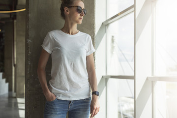 Front view.Young woman in sunglasses,white t-shirt and jeans standing near window in room with modern interior, with his hand in pocket of jeans. In background concrete wall.Mock up.