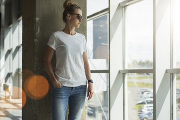 Front view. Young woman in sunglasses,white t-shirt and jeans standing near window in room, with his hand in pocket of jeans. In background concrete wall. Girl looks out window.Mock up.