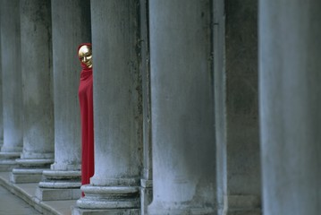 Carnival model in red cape and gold mask peering from columns in St. Mark's Square, Venice, UNESCO World Heritage Site, Veneto, Italy, Europe