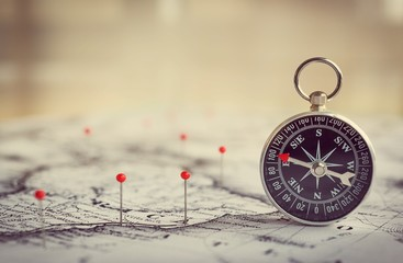 Wall Mural - Magnetic compass on a world map conceptual of global travel , tourism and exploration. Macro photo.