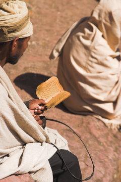 Pilgrim reads Holy Bible in Bet Maryam (St. Mary's) courtyard, Lalibela, Ethiopia