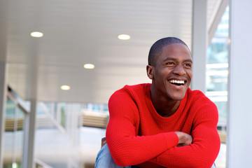 Portrait of young african man laughing with crossed arms