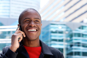 Close up happy african guy talking on mobile phone