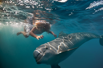 A little girl diving with dolphin underwater in deep blue sea