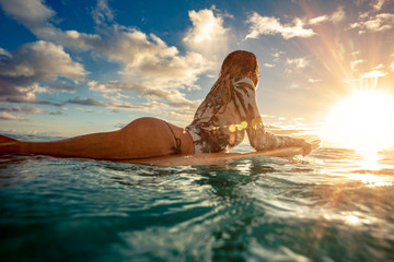 A surfer girl watching sunset on a surboard floating in green blue ocean lit with sun flare