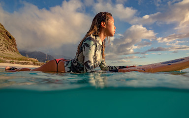 A surfer girl watching sunset on a surboard floating in blue ocean near rocky shore