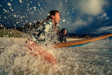 Two surfer girls standing in water wave splashes surrounded by drops ready to start surfing with surfboards