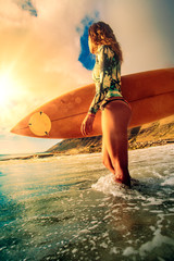 Surfer girl holding a board watching water condition and ready to go in the ocean at sunset time