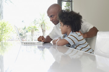 Side view of father and son using laptop at dining table