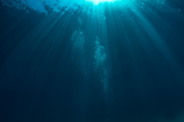 Air bubbles underwater in deep blue ocean with sunrays and water surface